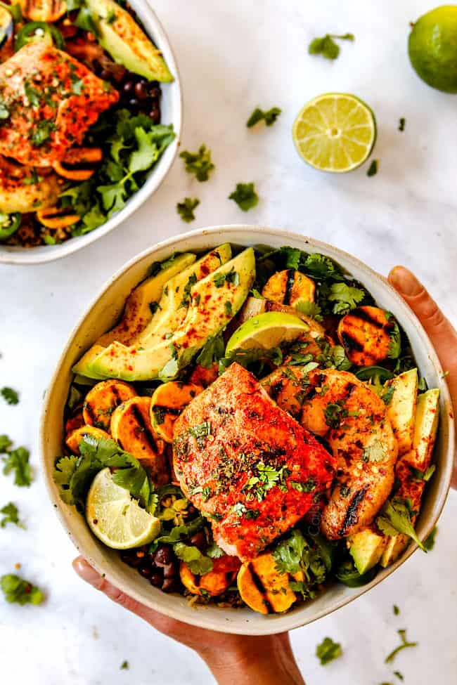 two hands holding easy salmon bowl recipe