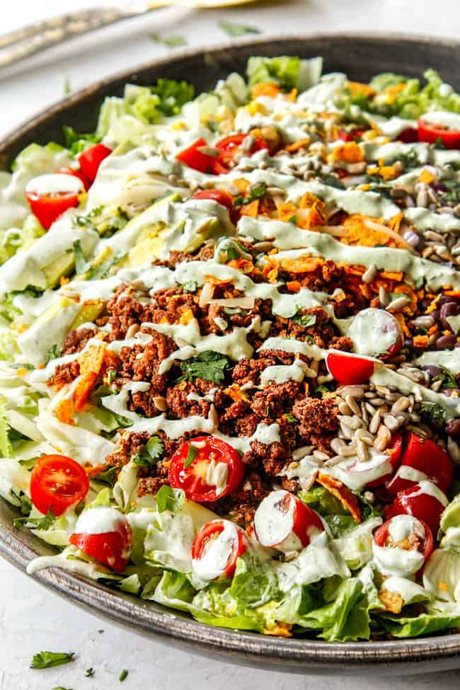A bowl of healthy taco salad drizzled with taco salad dressing