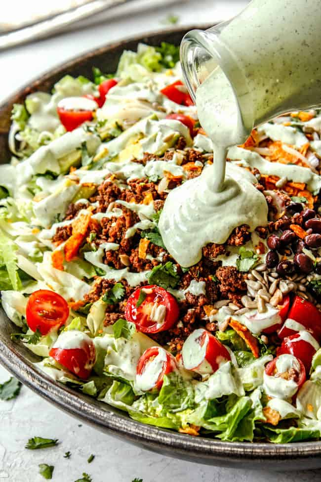showing how to make taco salad by pouring taco salad dressing over salad
