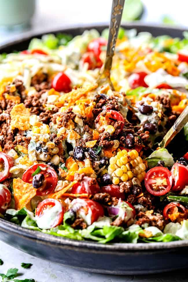 side view showing how to make taco salad by tossing salad ingredients together