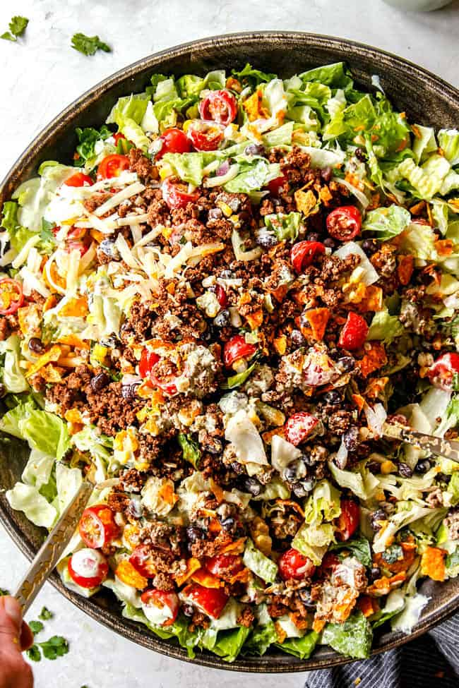 showing how to make taco salad by tossing all of the salad ingredients together
