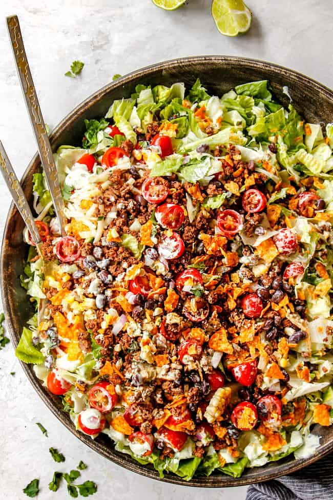easy taco salad recipe in a large wooden bowl with tongs
