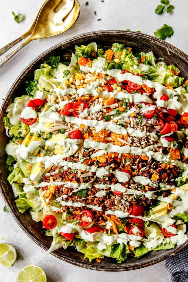 showing how to serve taco salad by layering taco salad ingredients