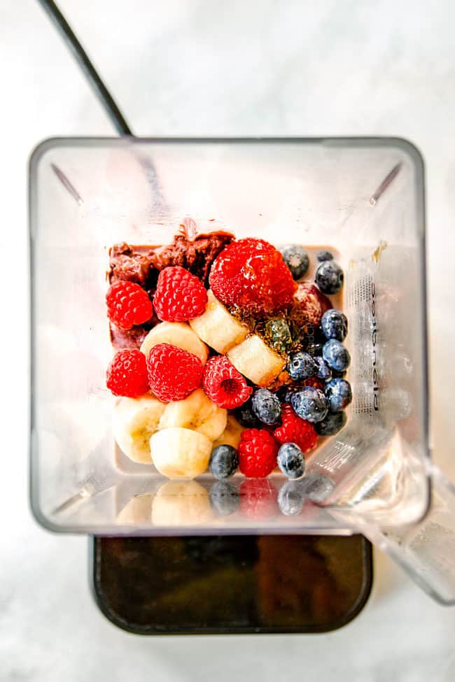 showing how to make berry acai bowls by adding bananas, strawberries, blueberries and milk to blender