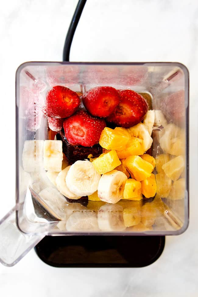 showing how to make acai bowl with pineapple, bananas, strawberries, pineapple juice in blender