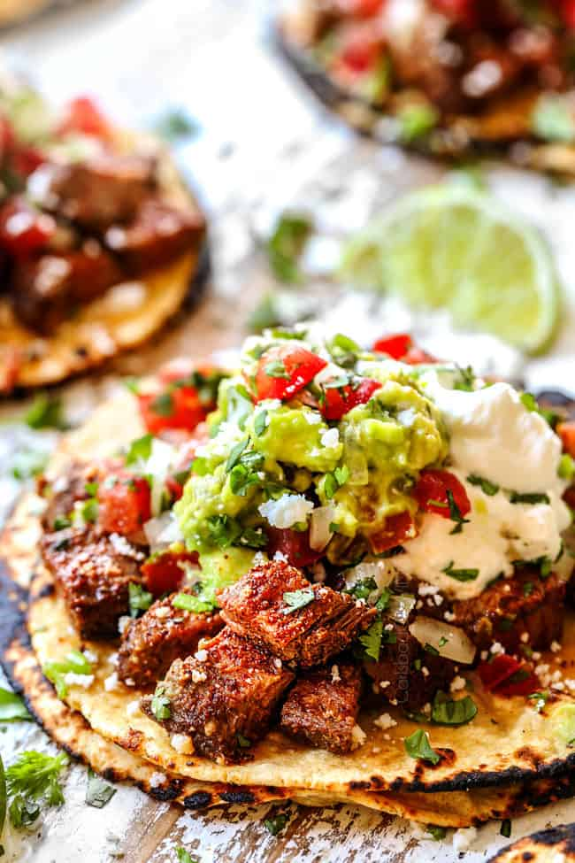 showing how to assemble marinated carne asada tacos by layering with carne asada, sour cream, guacamole, pico de gallo