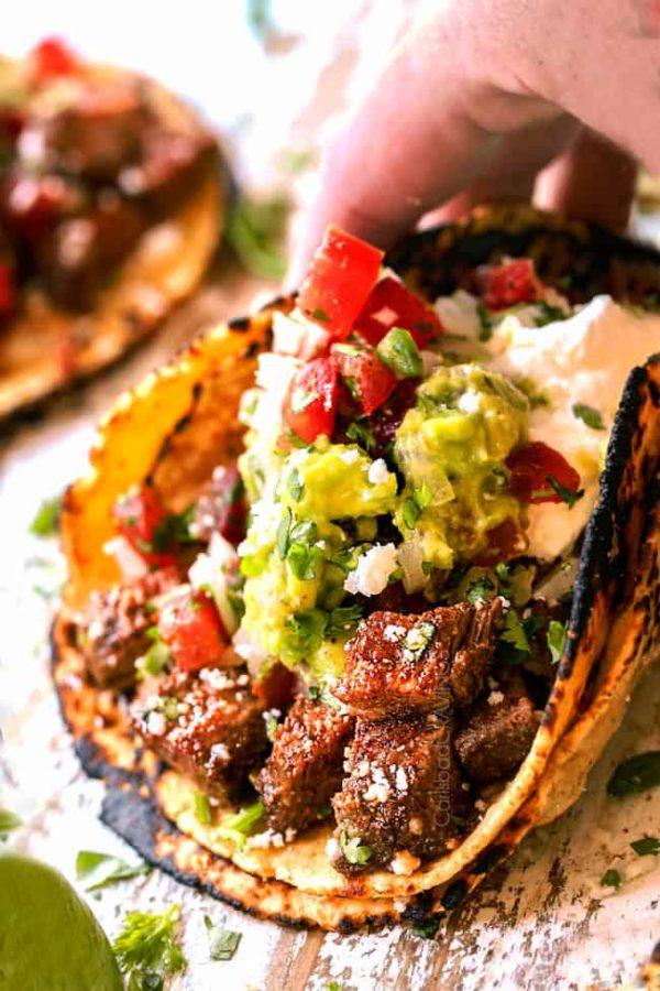 a hand holding a carne asada street taco ready to eat