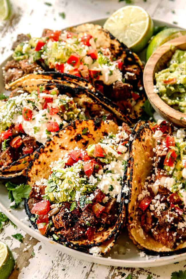 authentic Mexican street tacos lined up on a plate with