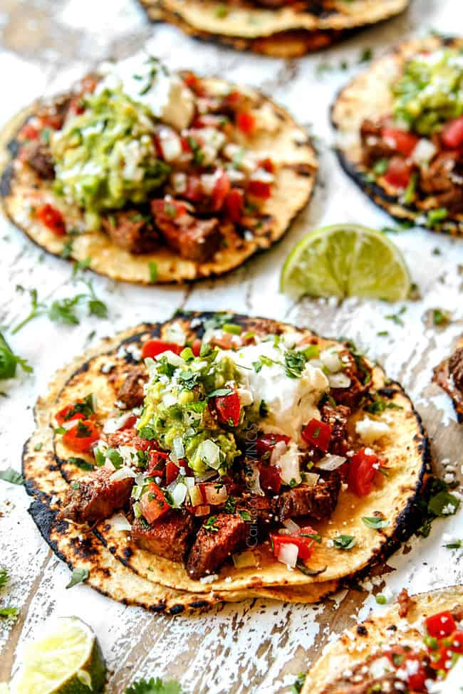 carne asada street tacos laying flat loaded with carne asada, guacamole, pico de gallo
