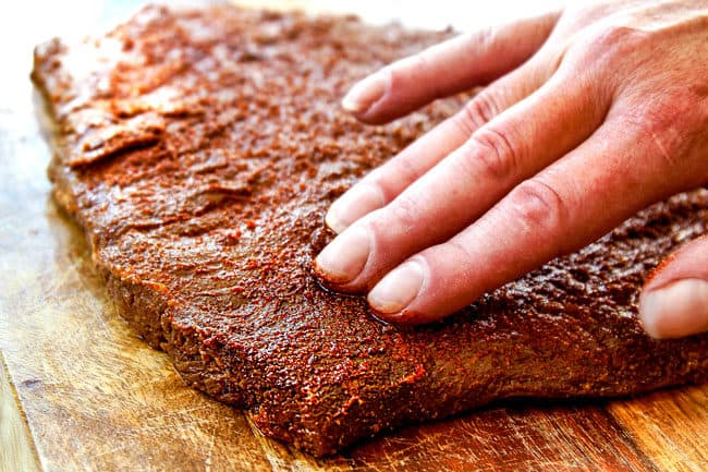 showing how to make carne asada by massaging a rub all over steak