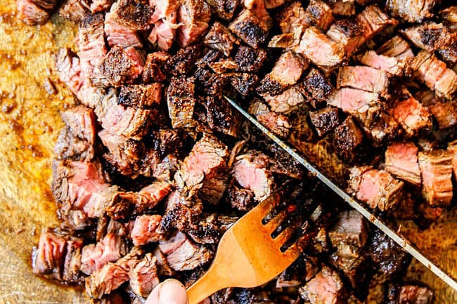showing how to make carne asada tacos by chopping steak into small pieces