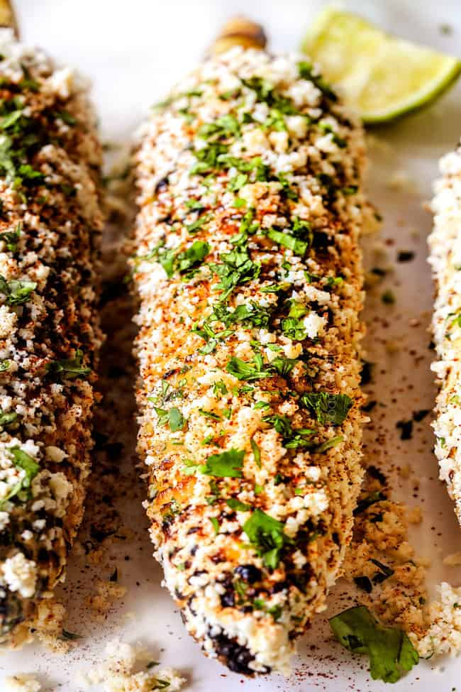 front up close view of elote Mexicano with mayonnaise, sour cream, cilantro, lime and queso fresco