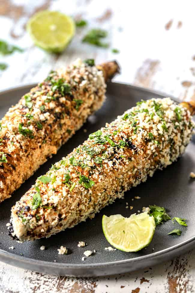 two pieces of elotes mexicanos on a gray plate garnished with lime