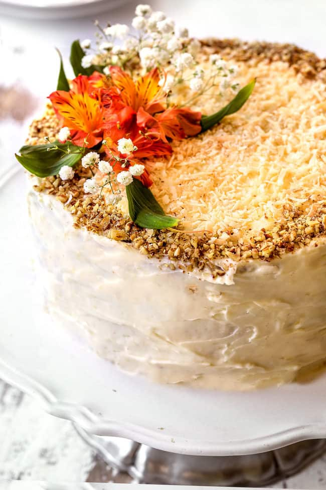 showing how to decorate hummingbird cake recipe with coconut and pecans on top of cake with flowers