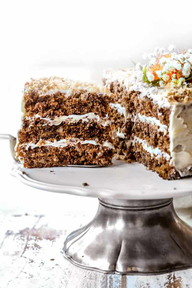 showing how to serve best hummingbird cake on a cake pedestal with slice cut out