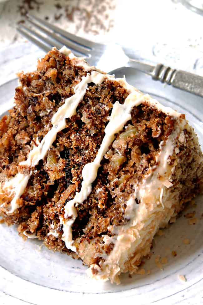 easy hummingbird cake on a white plate with cream cheese frosting, bananas, pineapple, pecans coconut