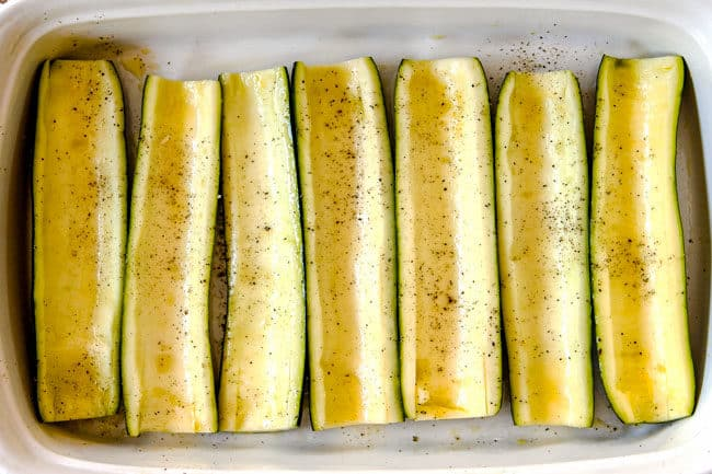 showing how to make zucchini boats by lining zucchini boats in a 9x13 baking dish