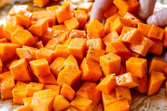 showing how to roast butternut squash by tossing with olive oil and seasonings