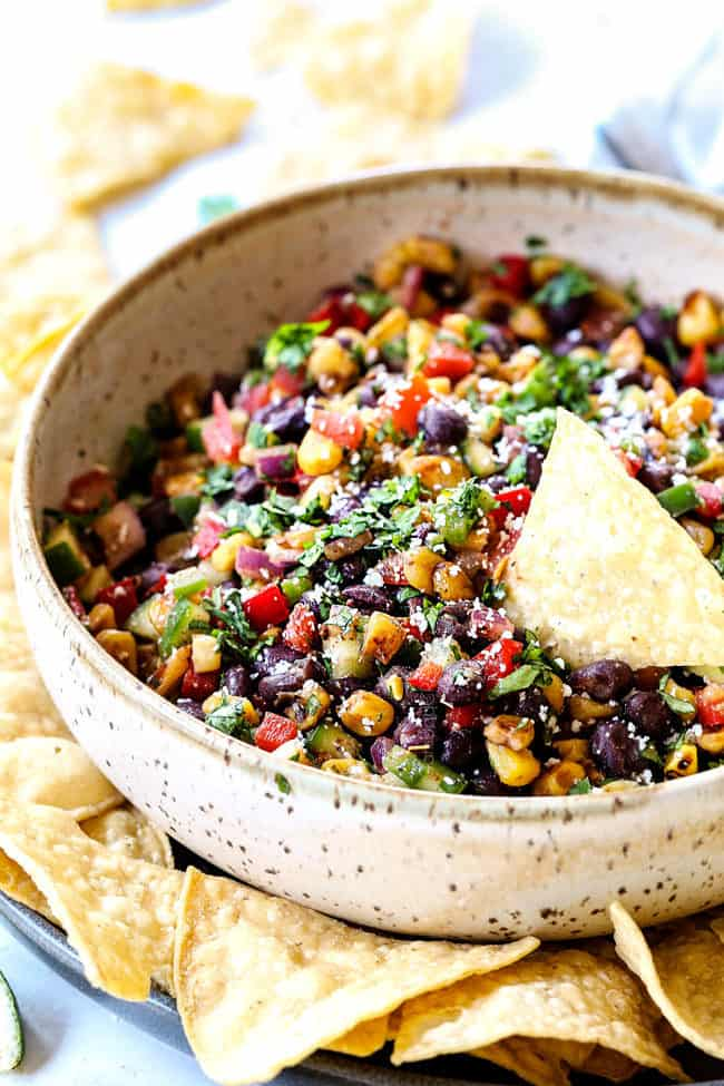 black bean corn salsa in a serving bowl with a chip dipping into it