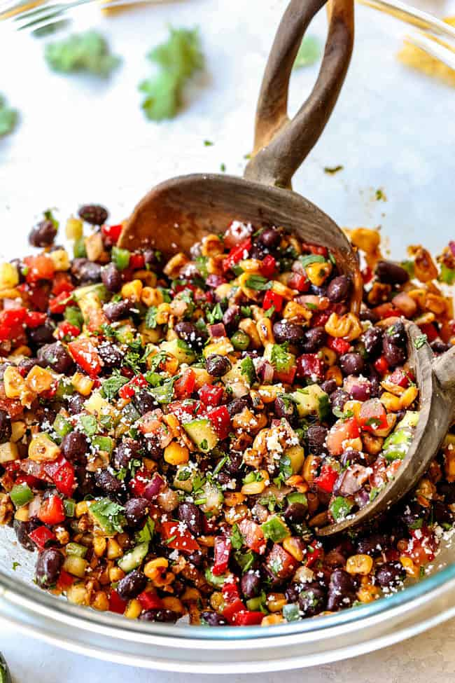 two tongs tossing black bean corn salsa ingredients together in a glass bowl
