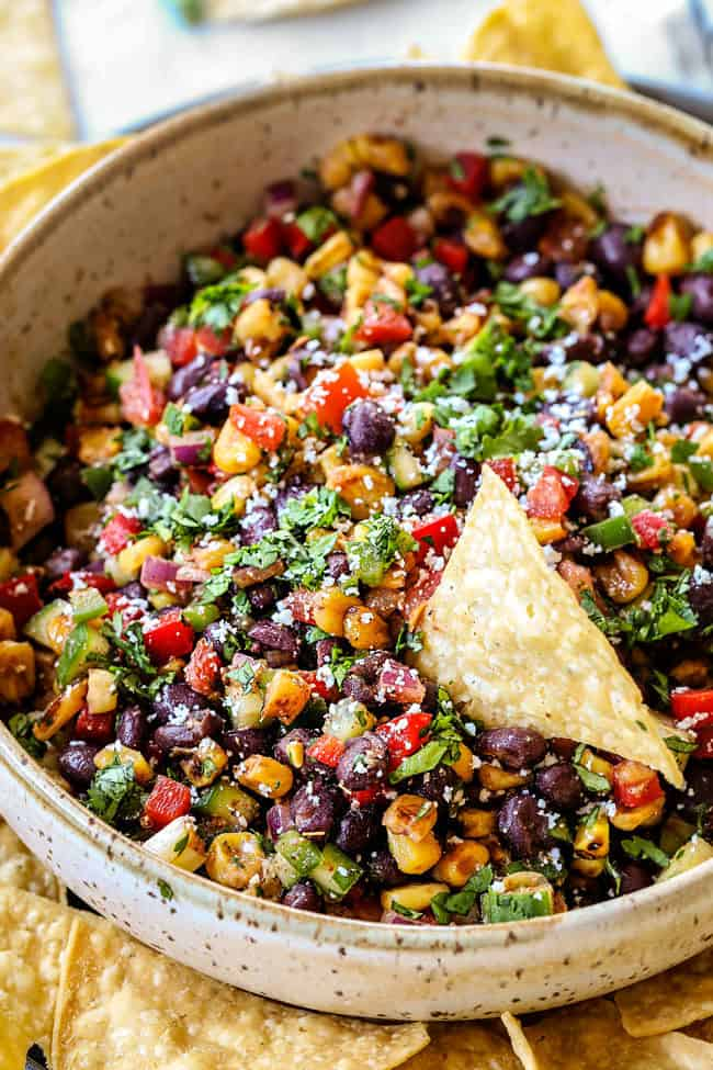 a big bowl of black bean corn salsa recipe surrounded by chips
