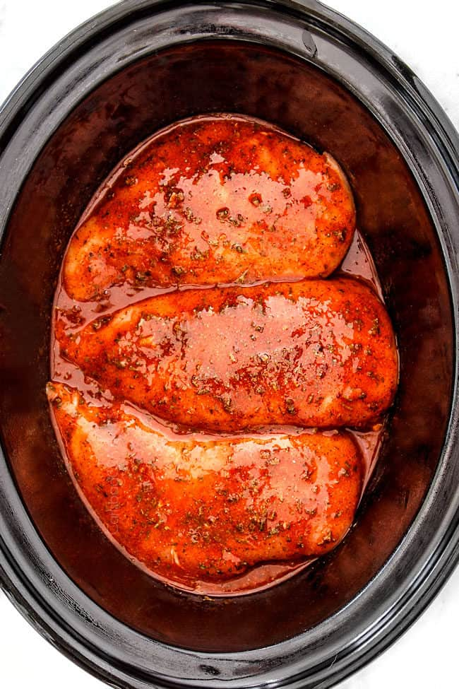 showing how to make crockpot buffalo chicken by adding chicken and buffalo sauce to a slow ooker