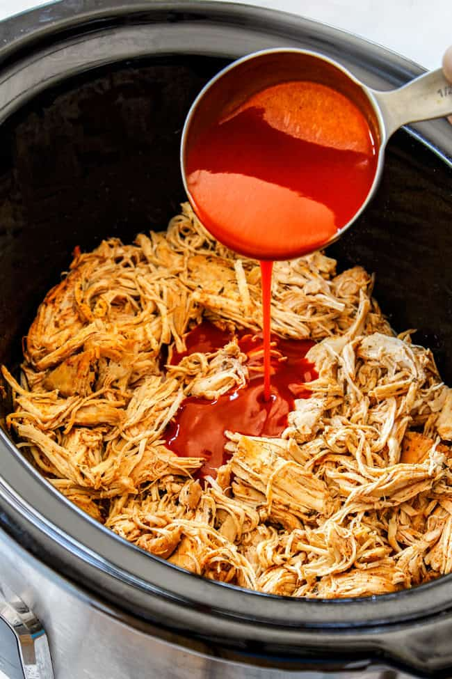 crockpot buffalo chicken by adding buffalo sauce to shredded chicken