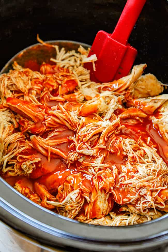 crockpot buffalo chicken by stirring buffalo hot sauce into chicken