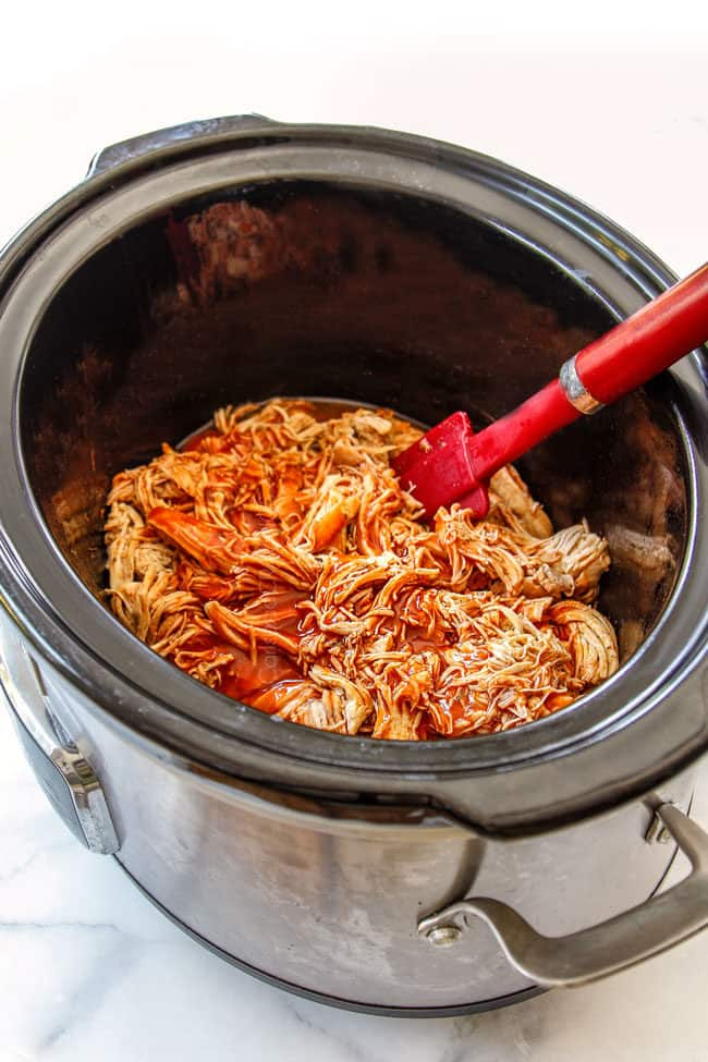 showing how to make slow cooker buffalo chicken by stirring hot sauce into shredded chicken