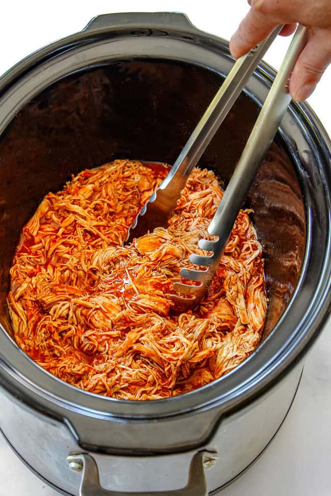 serving healthy slow cooker buffalo chicken with tongs