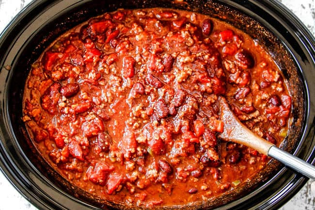 showing how to best crockpot chili recipe by stirring all the ingredients in the slow cooker