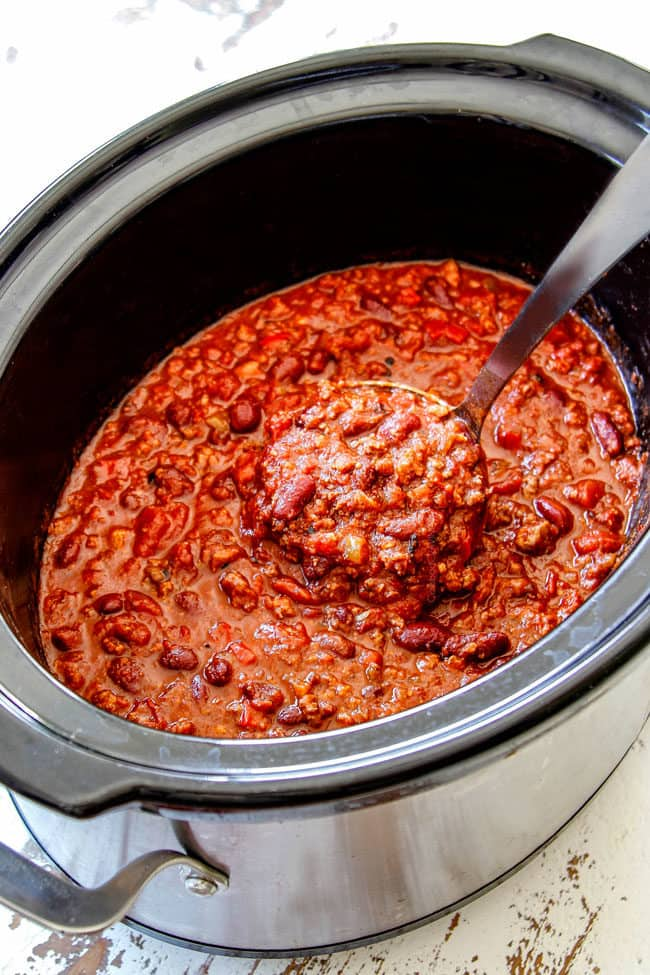 a ladle scooping up slow cooker chili recipe with beef and Italian sausage