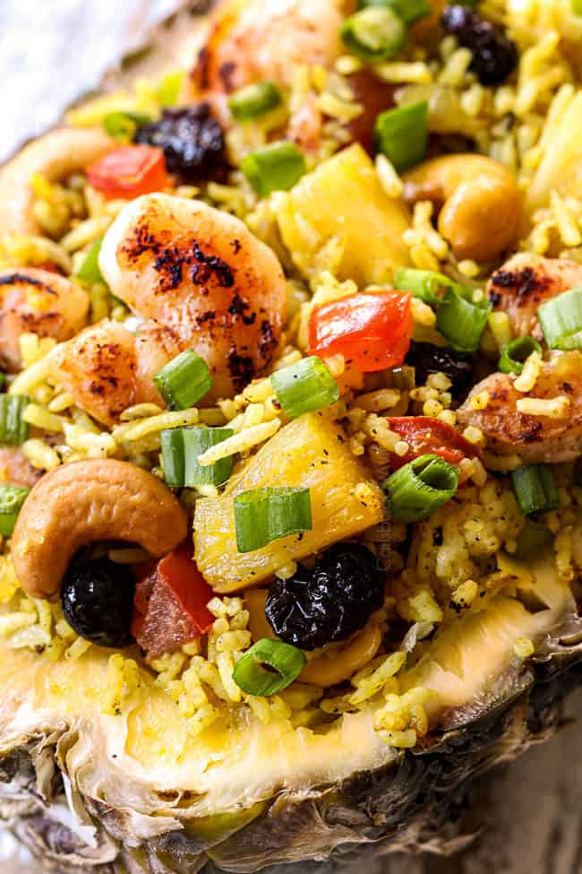 up close of pineapple fried rice with shrimp, cashews, green onions, tomatoes in a hollowed out pineapple