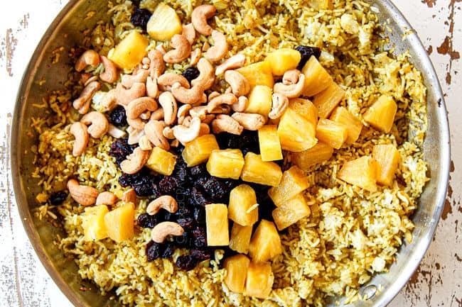 showing how to make pineapple fried rice by adding pineapple, cashews, craisins