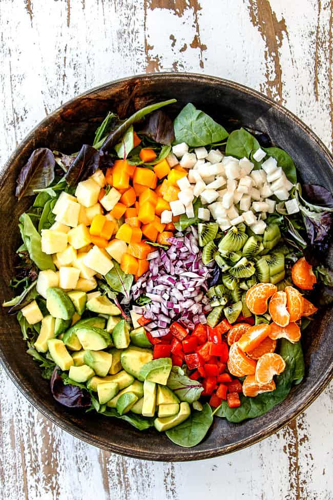 showing how to make shrimp avocado salad recipe by adding avocados, pineapple, mangos, jicamo, kiwis, red onion, bell peppers ad Mandarin oranges to a wood bowl