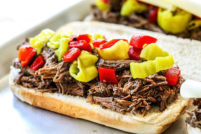 showing how to make slow cooker Italian Beef sandwiches by layering Italian Beef recipe with pepperoncini and roasted red bell peppers