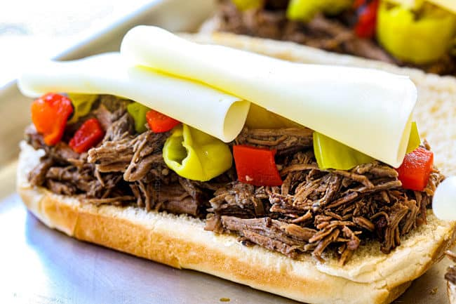 showing how to make crock pot Italian Beef sandwiches by layering the pepperoncini and roasted red bell peppers with provolone cheese