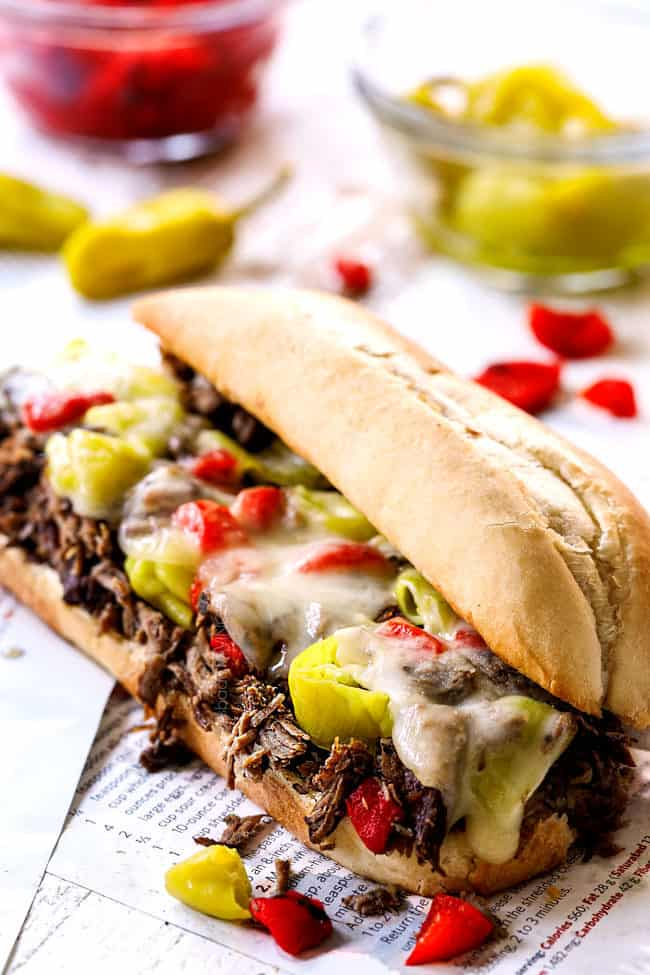 showing how to make Italian Beef Sandwich recipe by melting cheese over Italian Beef and toppings