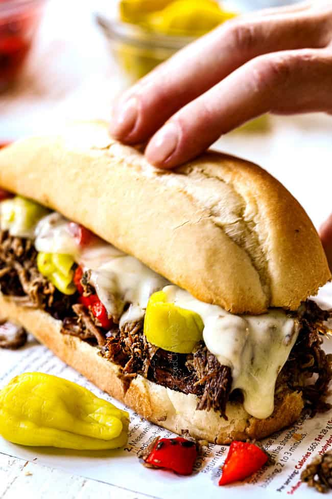 a hand picking up an Italian Beef Sandwich