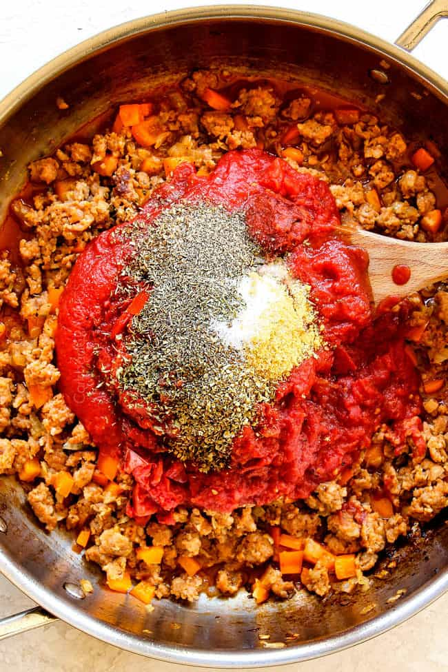 showing how to make rigatoni by adding crushed tomatoes, basil, parsley, oregano to sausage