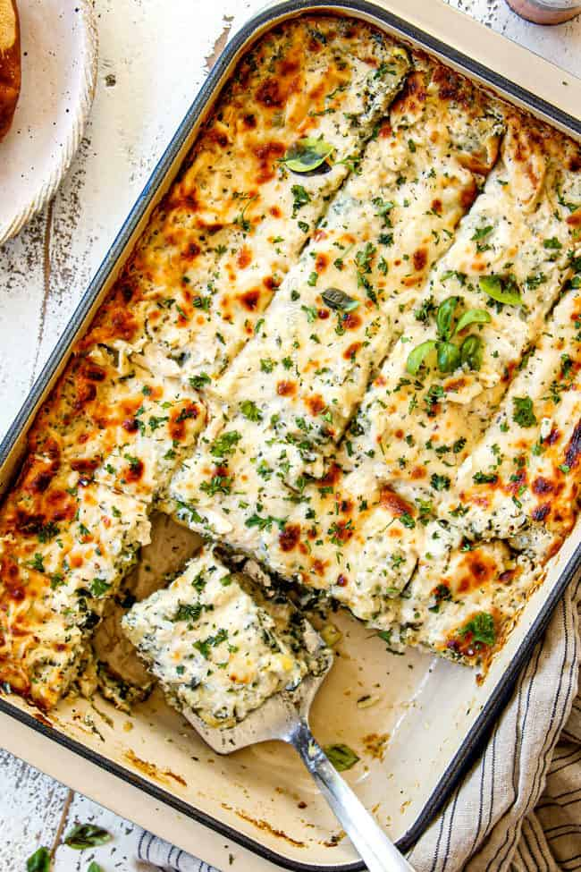 showing how to serve white chicken lasagna with a spatula