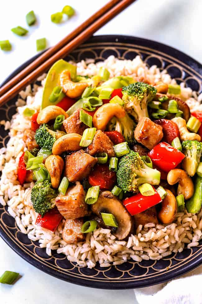 showing how to serve healthy chicken stir fry serving it over a big bowl of brown rice