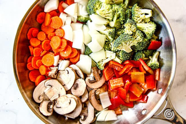 showing how to make easy chicken stir fry recipe by adding onions,s broccoli, carrots, bell peppers and mushrooms to skillet