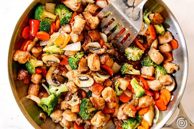 showing how to make easy chicken stir fry recipe by adding chicken and chicken stir fry sauce to vegetables in skillet