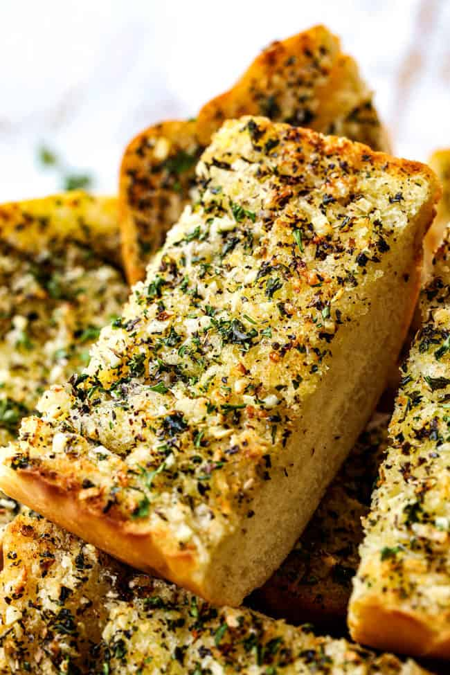 up close of a piece of the best garlic bread recipe in a bowl garnished with parsley