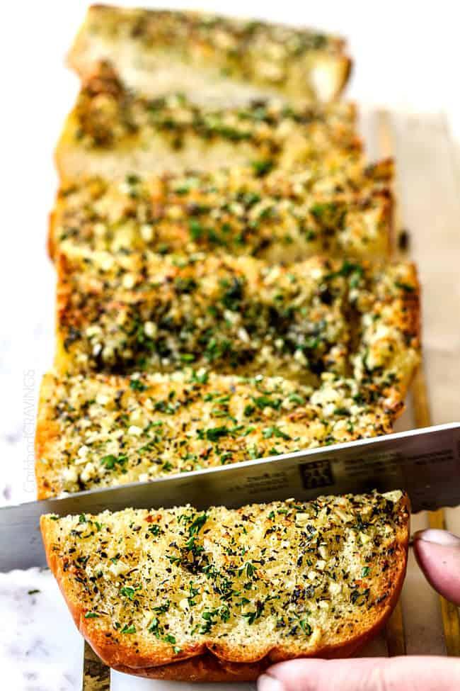 slicing easy garlic bread on a cutting board