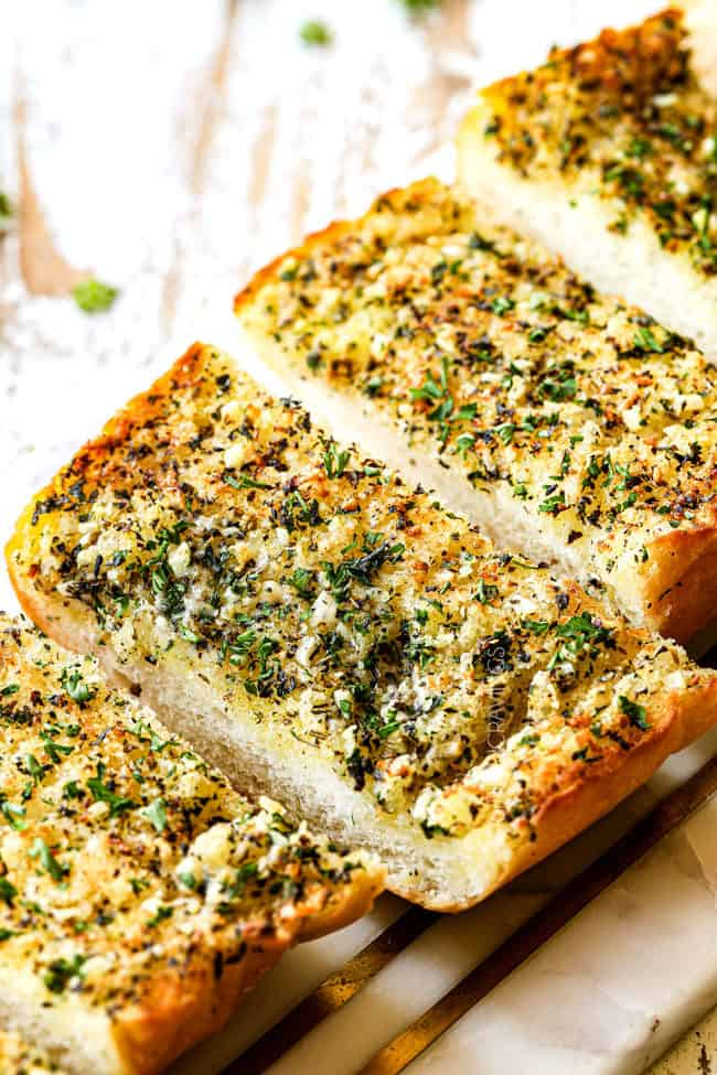 slices of the best garlic bread recipe on a marble cutting board garnished with parsley