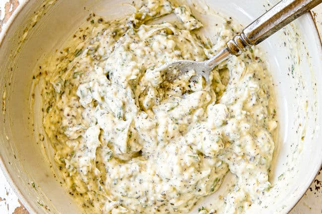 showing how to make garlic butter spread for Garlic Bread by mixing butter, garlic and herbs in a bowl until combined