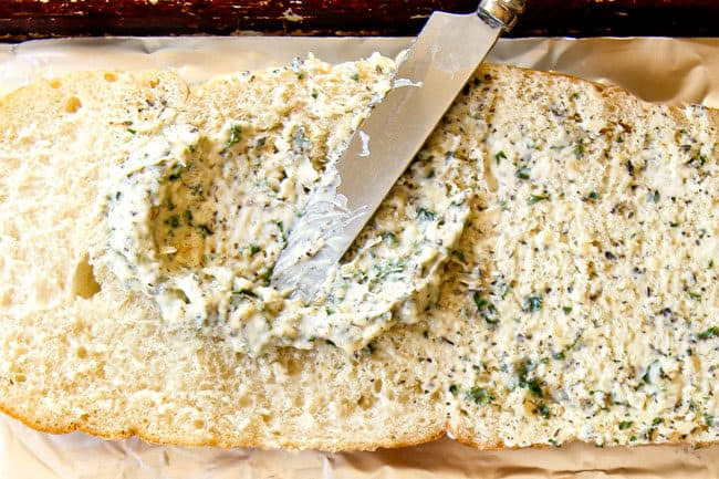 up close showing how to make garlic bread recipe by spreading garlic butter spread with a knife on bread