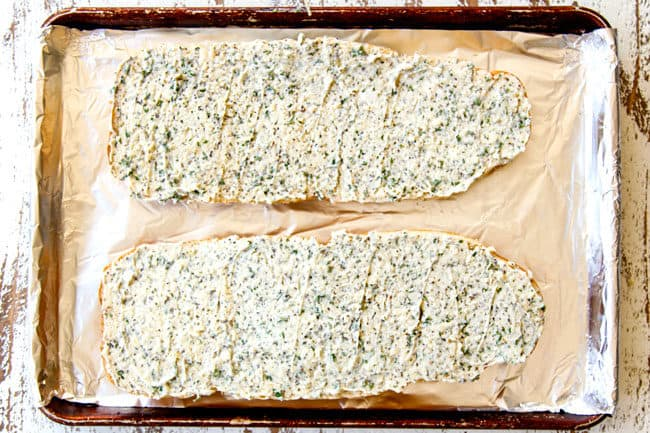 showing how to make homemade garlic bread by spreading garlic butter spread on french bread in an even layer